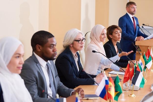 ビジネス会議で外国の代表に彼女の視点を説明する伝統的なヒジャーブのイスラム教徒の女性の1人 Premium写真