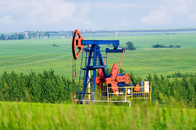 One oil pump extract oil in the middle of green fields Premium Photo