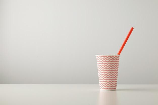 빨간 선 패턴으로 장식 된 한 종이 컵과 흰색 테이블에 고립 된 내부 빨대를 마시는 무료 사진