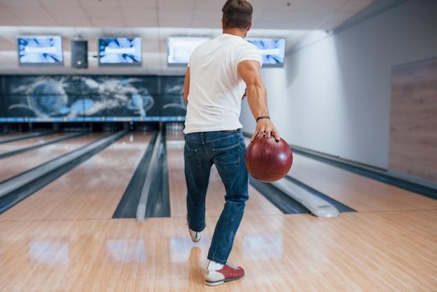 Только один человек. вид сзади человека в повседневной одежде, играющего в боулинг в клубе Бесплатные Фотографии