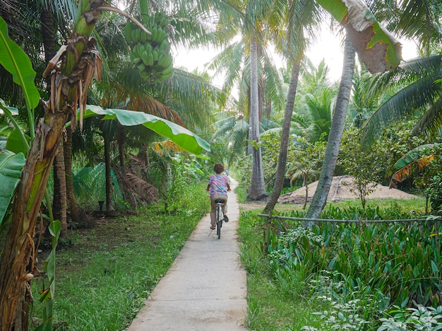 Один человек на велосипеде в районе дельты меконга, бен тре, вьетнам Premium Фотографии