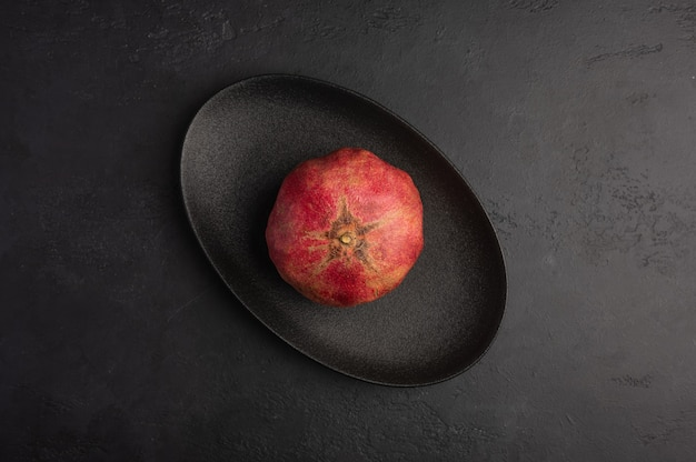 One pomegranate in the peel served in black oval plate on moody dark background. top view, healthy diet concept, copy space Premium Photo