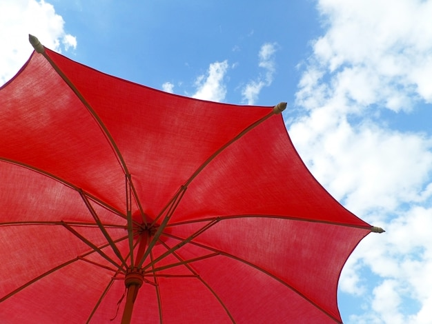 8414fa31e One red colored sunshade against vivid blue sky and fluffy white clouds  Premium Photo