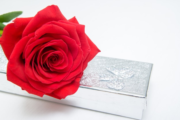 One red rose and jewelery present box on white wooden background Premium Photo