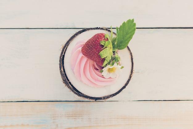 イチゴとクリームチーズの木製のテーブルに1つの半分のココナッツ。健康食品のコンセプトです。トーン画像、上面図 Premium写真