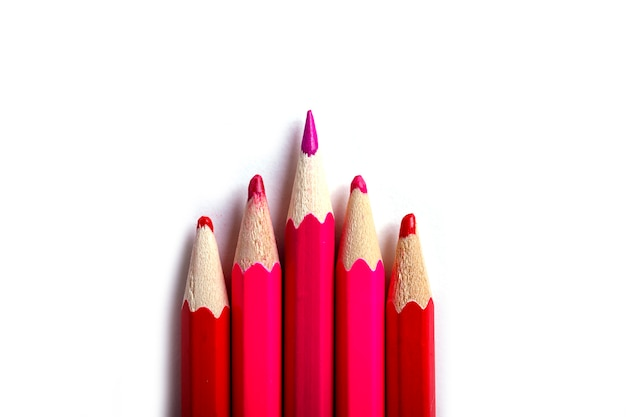 One sharpened pencil standing out from the blunt ones. it's easy to be beautiful if you do nothing concept. red pencils on white. Premium Photo
