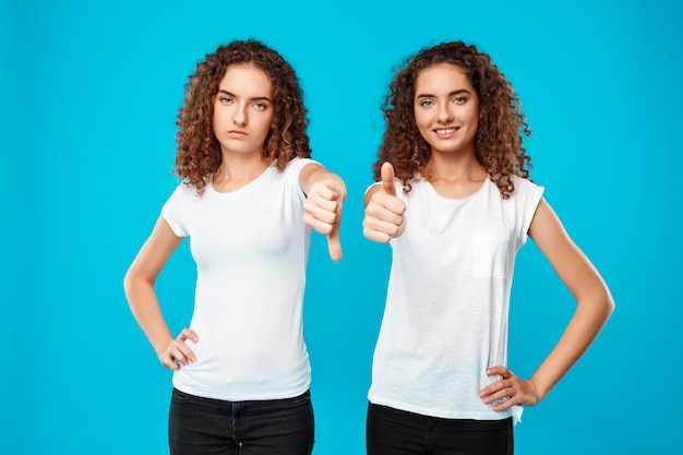 One of sisters twins showing dislike, another like over blue. Free Photo