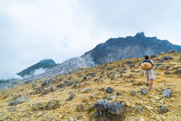 One tourist climbing sibayak volcano, active caldera steaming, sumatra indonesia Premium Photo