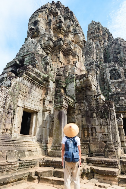 One tourist visiting angkor ruins amid jungle, angkor wat temple complex, travel destination cambodia. woman with traditional hat, rear view. Premium Photo