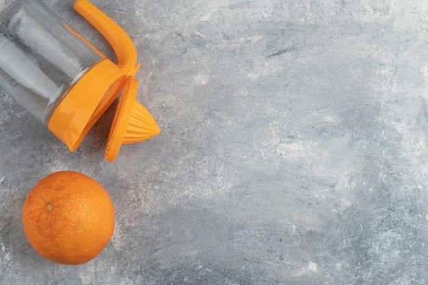 대리석 배경에 빈 유리 투 수와 함께 하나의 전체 건강한 오렌지 과일. 무료 사진