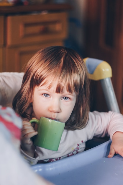 A one-year-old smiling girl sits at a children's table in a high chair and eats with a spoon from a bowl. colored background. healthy eating for kids. baby food. Premium Photo