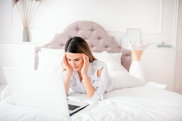 One young woman of 25 years of european appearance lies on a bed with a laptop at home on a white bed. feels an unhealthy headache or eye strain, bad news Premium Photo