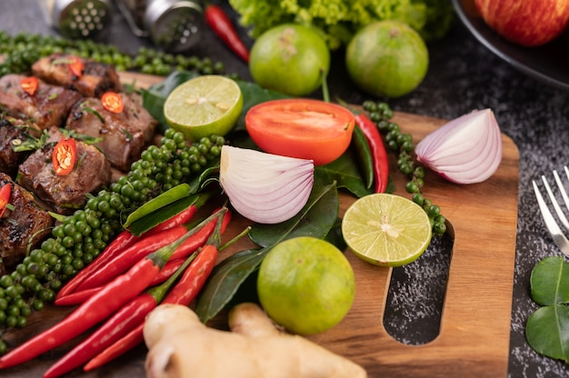 Onion, chili, fresh pepper kaffir lime leaves and lime placed on a wooden chopping board. Free Photo