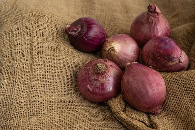 Onions with purplish-red skin on a jute mat Premium Photo
