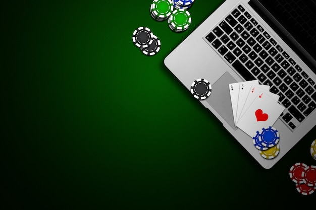 Online casino, laptop, chips cards on green Premium Photo