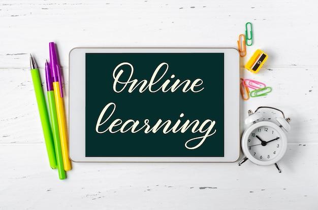 온라인 학습-태블릿에 필기 비문. 어린이를위한 원격 훈련의 개념. 흰색 나무 바탕에 태블릿 및 사무 용품. 프리미엄 사진