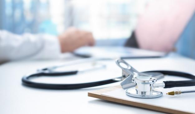 オンライン医学の概念。バックグラウンドで医師の職場に聴診器とクリップボード、医師はラップトップを使用してオンライン患者相談を実施します Premium写真