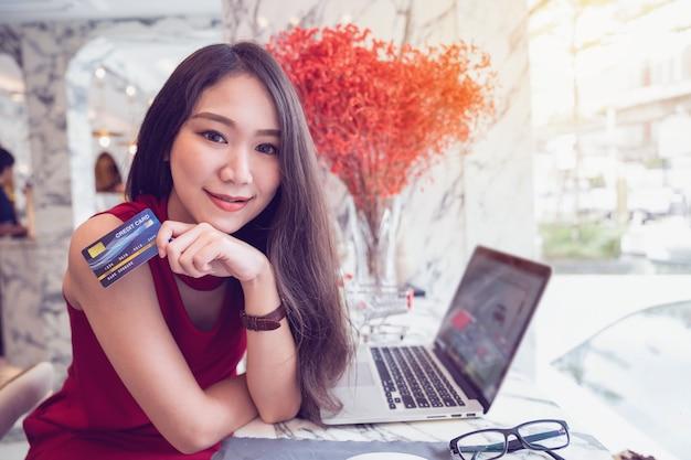 Концепции онлайн оплаты, молодая азиатская женщина, улыбаясь, держа в руках кредитную карту, делая покупки онлайн на ноутбуке в кафе Premium Фотографии