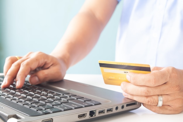Online payment, man's hands holding a credit card and using laptop for online shopping Premium Photo