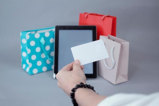 オンラインショッピングの概念。白い画面と美しいギフトバッグのあるタブレットのモックアップの壁に対して、女の子は彼女の手にクレジットカードを持っています。 Premium写真