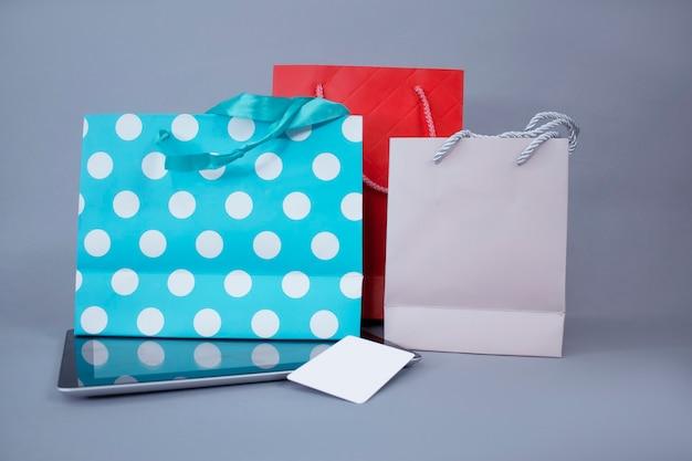 オンラインショッピングの概念。白い画面と明るいギフトバッグの壁にクレジットカードをクローズアップタブレットモックアップ。 Premium写真