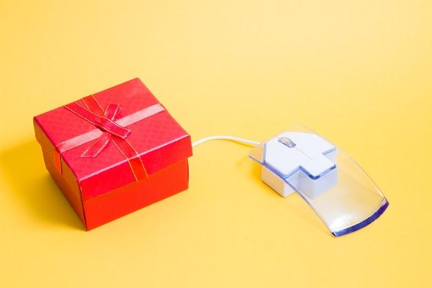 온라인 쇼핑 개념, 컴퓨터 마우스 및 선물 상자, 노란색 배경, 복사 공간 프리미엄 사진