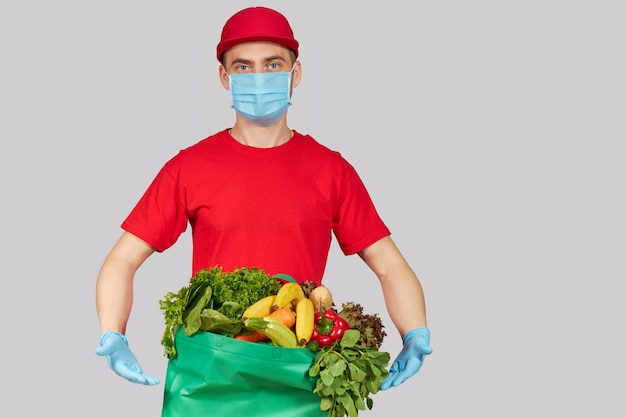 オンラインショッピングの概念。赤い制服を着た男性宅配便、防護マスク、新鮮な果物と野菜の食料品ボックス付き手袋。コロナウイルス検疫中の宅配食品 Premium写真