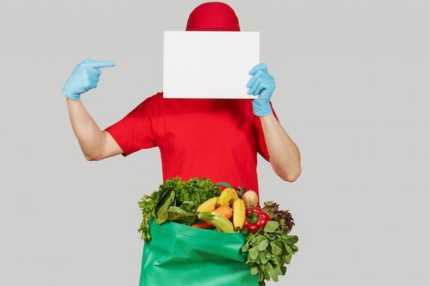 オンラインショッピングの概念。赤い制服を着た男性宅配便、防護マスク、手袋と果物と野菜の食料品の箱でテキストの白い旗を保持しています。検疫中の宅配食品 Premium写真