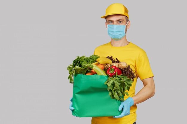 オンラインショッピングの概念。黄色の制服を着た男性の宅配便、防護マスク、手袋と新鮮な果物と野菜の食料品の箱。コロナウイルス検疫中の宅配食品 Premium写真