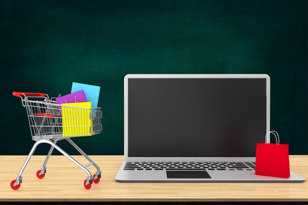 54a553019ca Online shopping concept. paper bags in shopping cart on wood table with laptop  keyboard.