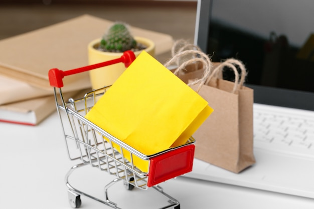 Online shopping concept. shopping cart, laptop on the desk Premium Photo