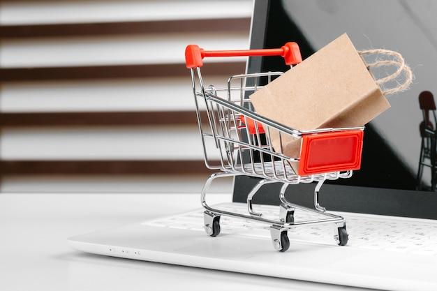 Online shopping concept, shopping cart, laptop on the desk Premium Photo