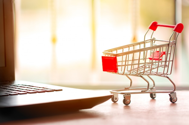 Online shopping concept. shopping cart, small boxes, laptop on the desk Premium Photo