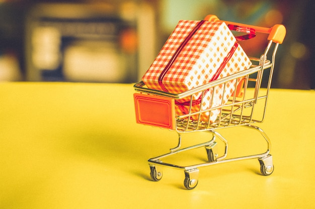 Online shopping concept - trolley cart full of presents. Premium Photo