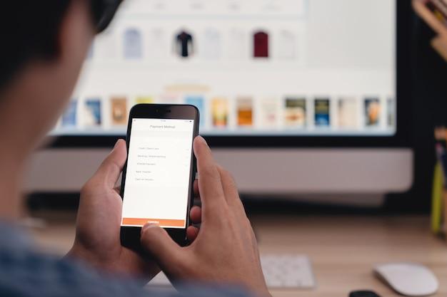 オンラインショッピングの概念-携帯電話でオンラインショップをしながら支払いを選択するアジア人 Premium写真