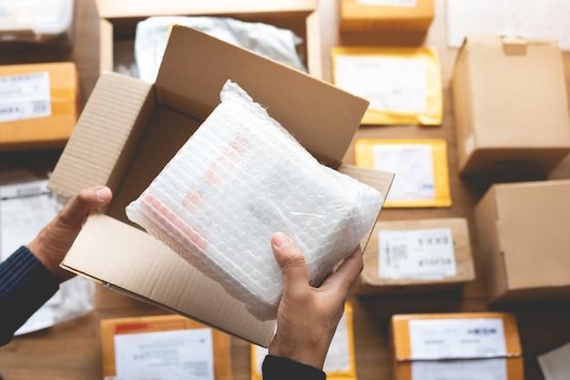 男性の手が茶色の箱にいくつかの製品を梱包するオンラインショッピングの概念 Premium写真
