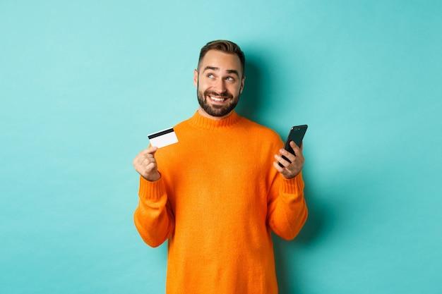 オンラインショッピング。考えているハンサムな男、クレジットカードでスマートフォンを持って、インターネットストアで支払い、明るいターコイズブルーの壁の上に立っています。 無料写真