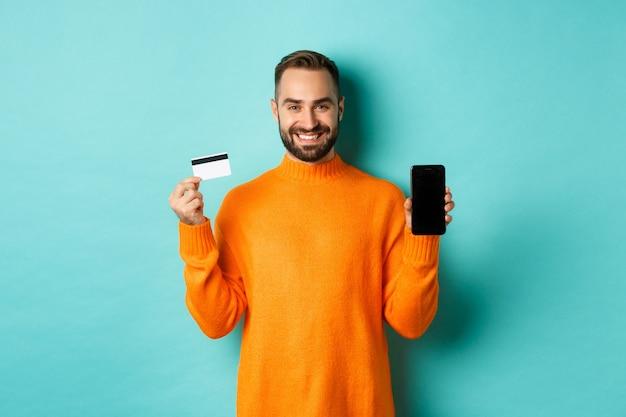 オンラインショッピング。携帯電話の画面とクレジットカードを見せて、満足して笑って、明るいターコイズブルーの壁の上に立って幸せな魅力的な男 無料写真