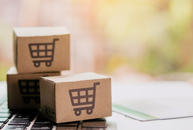 Online shopping - paper cartons or parcel with a shopping cart logo and credit card on a laptop keyboard. shopping service on the online web and offers home delivery. Premium Photo