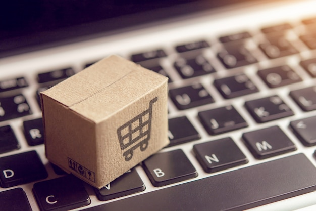Online shopping - paper cartons or parcel with a shopping cart logo on a laptop keyboard. Premium Photo