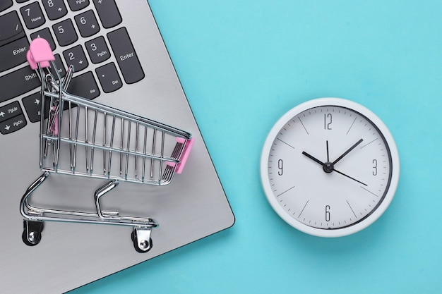 Online shopping time. computer keyboard with clock and supermarket trolley on a blue background. top view Premium Photo