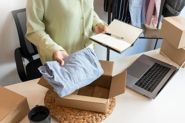 고객, 시작 및 온라인 비즈니스 개념을 제공하기 위해 제품을 준비하는 상점에서 일하는 온라인 소규모 기업가 상인. 프리미엄 사진