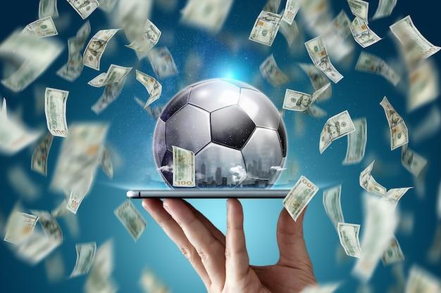 オンラインスポーツ賭博。スマートフォンとサッカーボールを持った手の背景にドルが下落している。創造的な背景、ギャンブル。 Premium写真