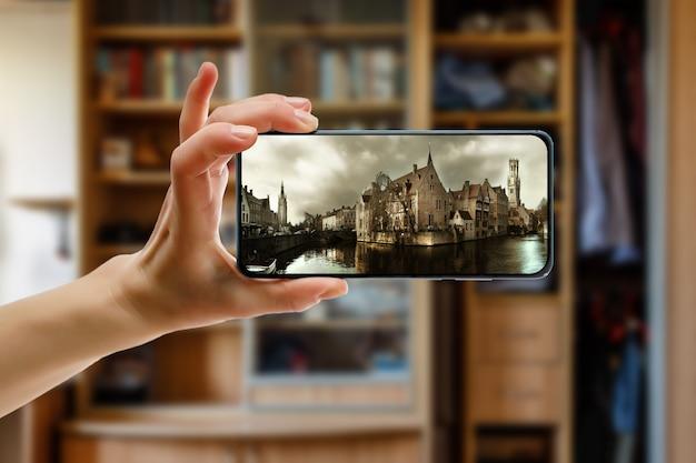 집에서 스마트 폰을 사용하여 벨기에의 유럽 구시 가지 브루 게로 온라인 여행. 프리미엄 사진