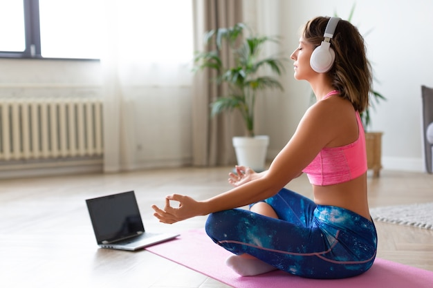 Online yoga lesson. woman in headphones in lotus position in front of laptop monitor. Premium Photo