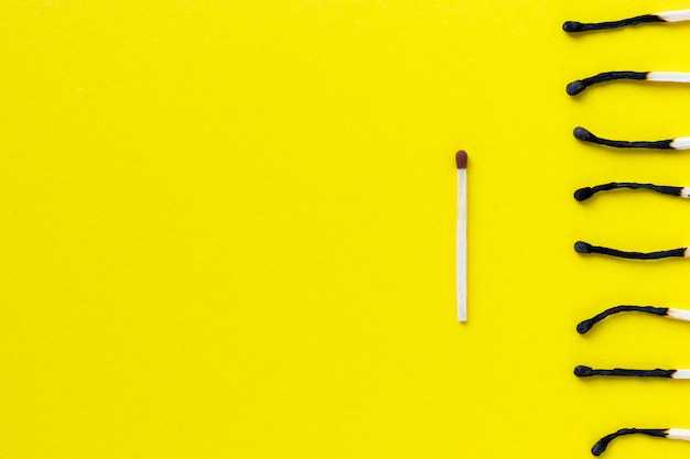Неиспользованные и сгоревшие спички на желтом фоне Premium Фотографии