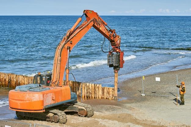 Ð¡ 해안의 나무 줄기에서 방파제 건설. 프리미엄 사진