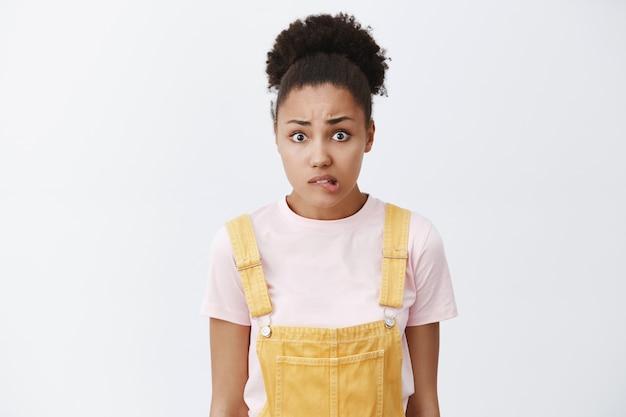 Ops, ho commesso un errore, sentendomi in colpa. ritratto di donna afro-americana insicura preoccupata con acconciatura panino, labbro mordace nervosamente e guardando, volendo chiedere scusa sul muro grigio Foto Gratuite