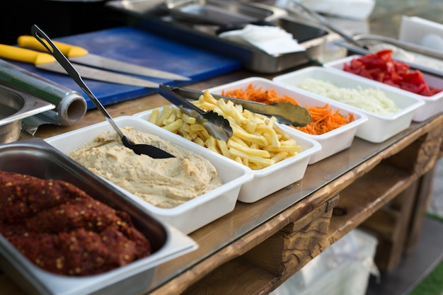 Open air kitchen products for cooking falafel in dishes on a wooden table. Premium Photo