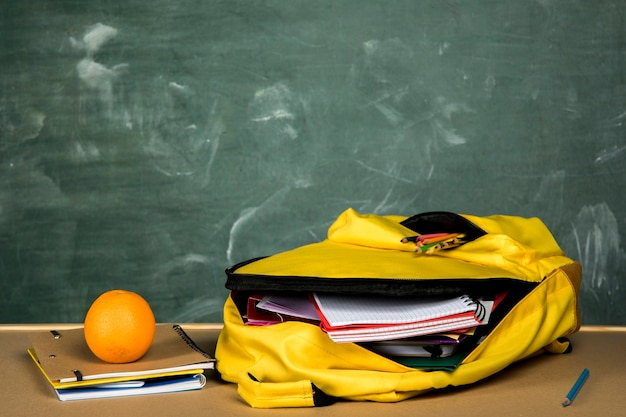 Open backpack and orange on table Free Photo